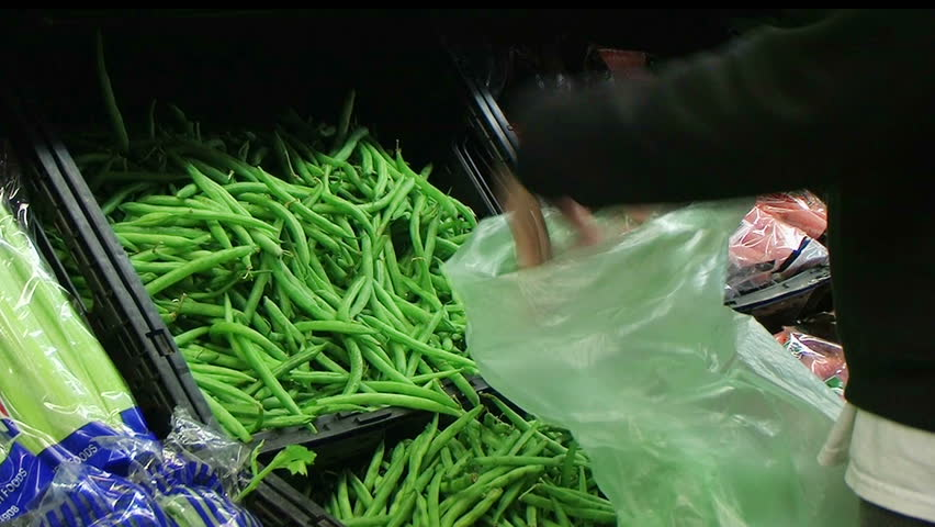 Woman selecting fresh green beans in grocery store produce department.