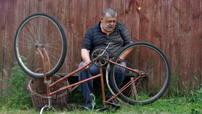 Bearded senior man is nervous about very old bicycle to repair sitting against wooden fence