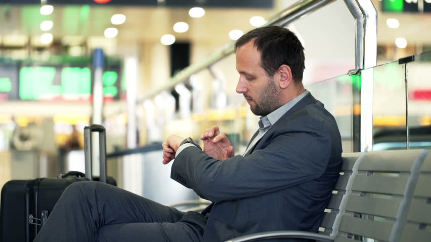 Young businessman using smartwatch while sitting at train station