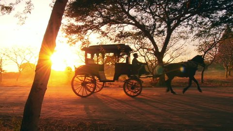 Retro transport in Burma, Bagan. Vintage horse wagon at sunset with shining sun and warm sun rays through trees and cart windows. Countryside of Myanmar