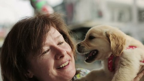 Woman kisses little puppy of golden retriever