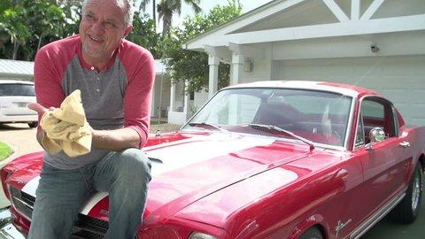 Retired Senior Man Sitting On Hood Of Restored Classic Car