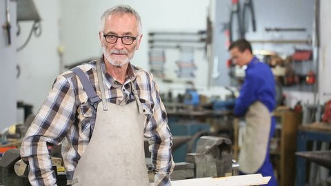 Senior craftsman in workshop with apprentice in background