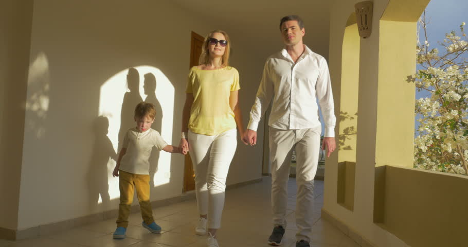 Steadicam shot of a mother, father and son walking over the hotel corridor. They're holding hands and talking with each other.   Shutterstock HD Video #10596212