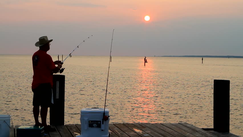 Senior adult man fishes from a pier as he watches the sun set in the background.