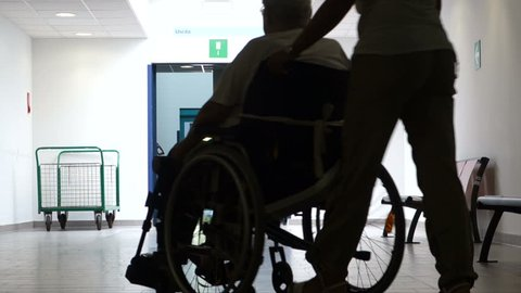 Backlighting of a nurse pushing a man in a wheel chair towards the light.