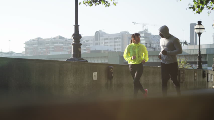 4K Athletic man and woman running together through urban environment #10621892
