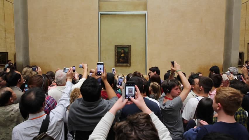 "PARIS - JUNE 1: Visitors take photo of Leonardo DaVinci's ""Mona Lisa"" at the Louvre Museum, June 1, 2015 in Paris, France. The painting is one of the world's most famous."