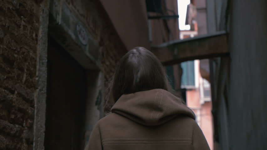 Slow motion of a happy young woman wandering among worn grungy buildings of old city and looking around   Shutterstock HD Video #10638302