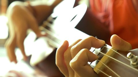4K Video : Little Asian child playing ukulele on sofa, Soft focus and vintage filter.