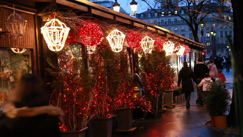 people walk at stalls with Christmas trees decorated lighted lanterns and illuminated in Paris evening