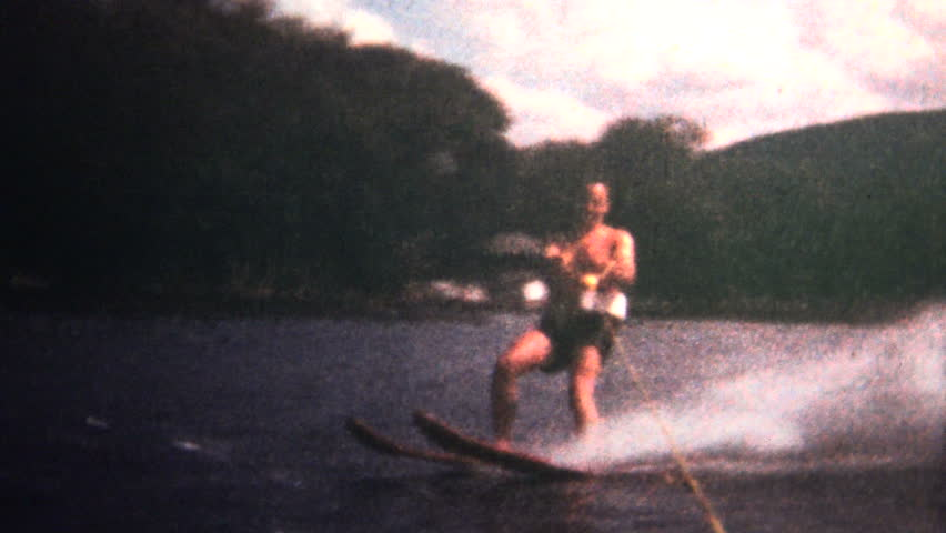 FORT WORTH, TEXAS - JULY 1966: Man waterskiing behind a boat showcases his skills on a hot summer day.