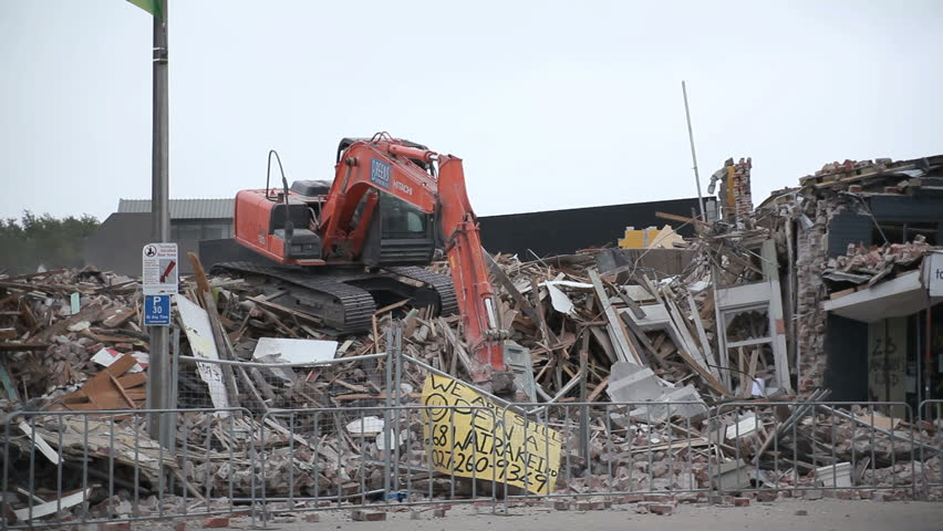 CHRISTCHURCH, NEW ZEALAND - FEB 23: A digger demolishes a local mall on the Feb 23rd, 2011. Damage caused by the Christchurch Earthquake, which devastated the city on Feb 22nd.