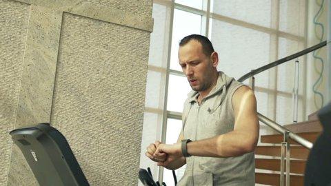 Man checking pulse on smartwatch on treadmill