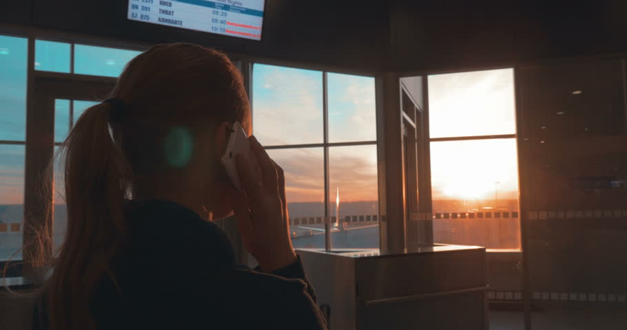 Woman in the terminal of airport talking on the phone and looking out the window with sunset scene | Shutterstock HD Video #10680596
