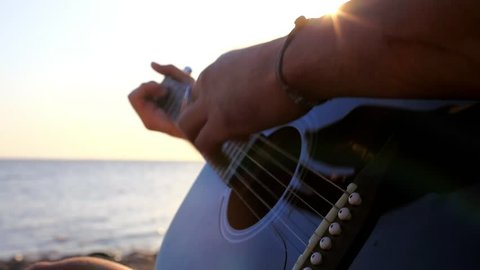 Musician hand playing guitar and he's sings song in the beach during sunset on blurred background and sunlight in sea.