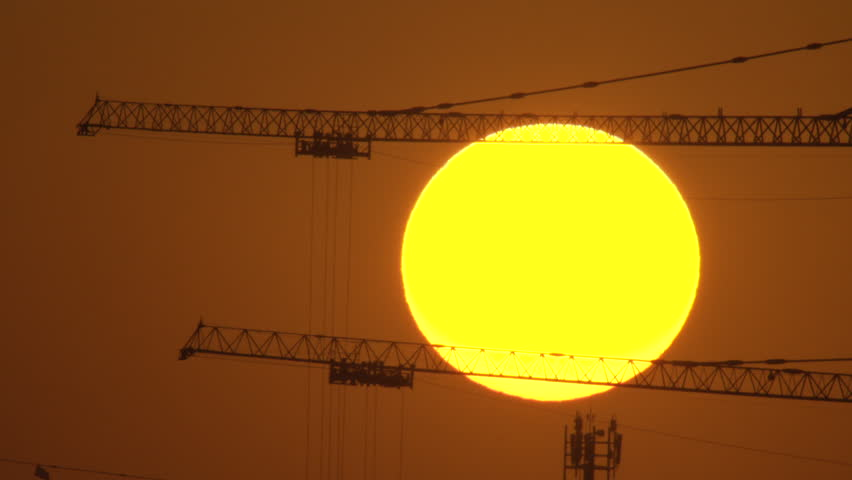 Large sun setting behind construction cranes in Doha Qatar | Shutterstock HD Video #10727522