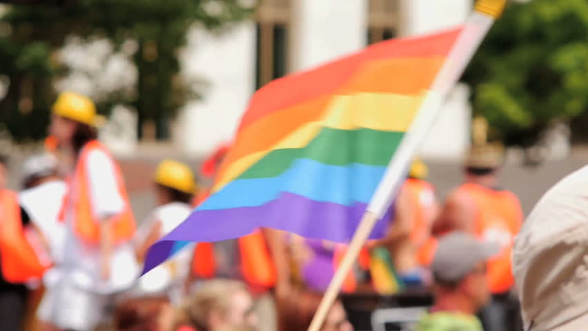 A Rainbow flag waves as a float of excited gay pride supporters pass by in the background. slow motion. Symbol of LGBT GLBT transgender rights love equality and freedom | Shutterstock HD Video #10756760
