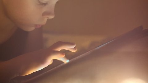 Close up of face and hands of 8 years old kid playing computer games lying in his bed in evening. Child using tablet pc.