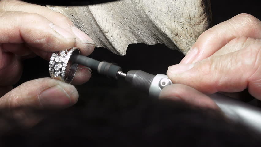 Goldsmith is polishing a gold or silver ring