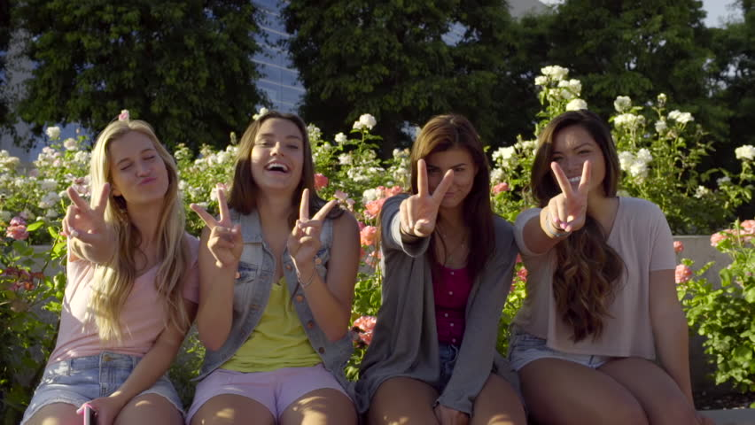 Group Of Teenage Girls Sit On A Wall In A Rose Garden And -6724
