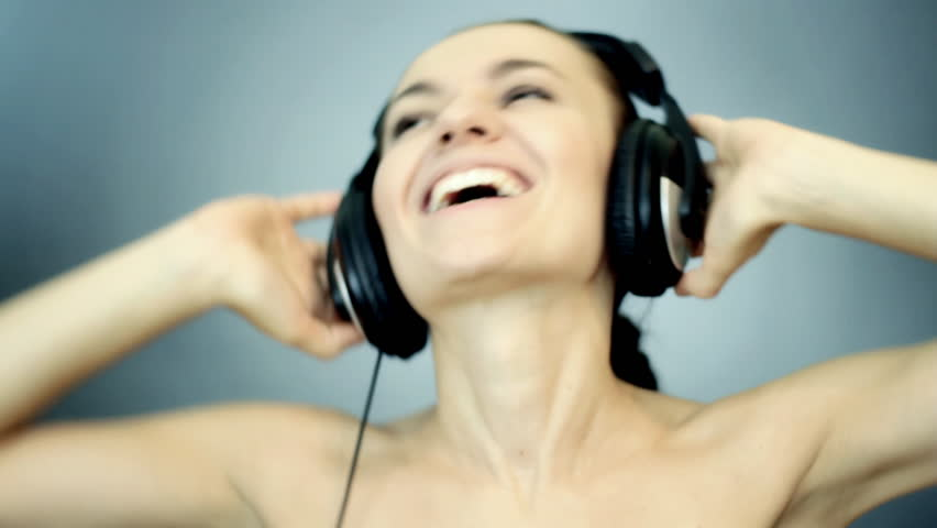 Beautiful woman with headphones listen to the music on blue background
