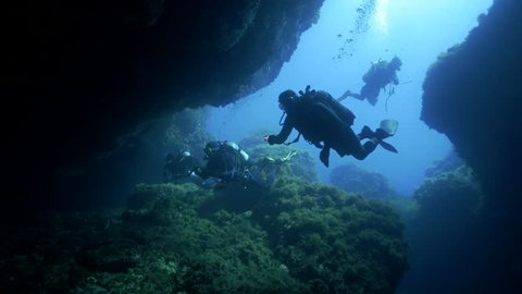 underwater shot of scuba divers entering a huge underwater cave in mediterranean sea, wide shot, ustica island, italy