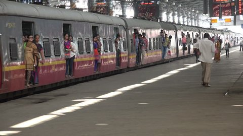 MUMBAI, INDIA - 6 NOVEMBER 2014: Passengers exit a carriage and enter the platform at the enormous Victoria Terminus train station in central Mumbai.