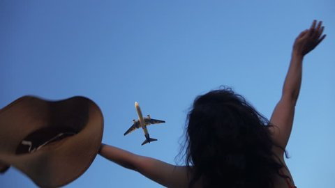 Airplane passing overhead, woman watching waving