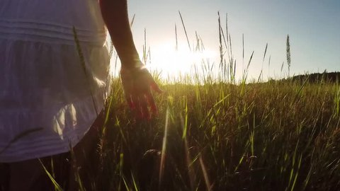 Young woman in white sundress walking through grassy field at sunset