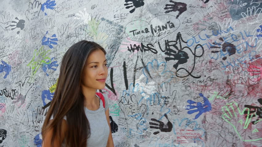 Berlin people - woman at Berlin Wall smiling happy in Germany. Beautiful multiracial Asian Caucasian woman looking to side during travel in Europe.