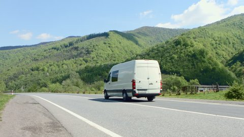 White van traveling at speed on the roads against the backdrop of mountains and pure summer sky