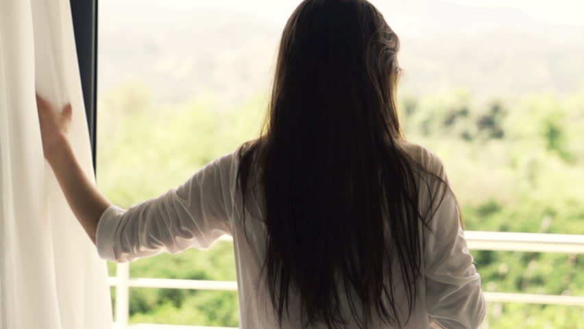 Young woman unveil curtain, walking out on terrace, slow motion shot at 240fps