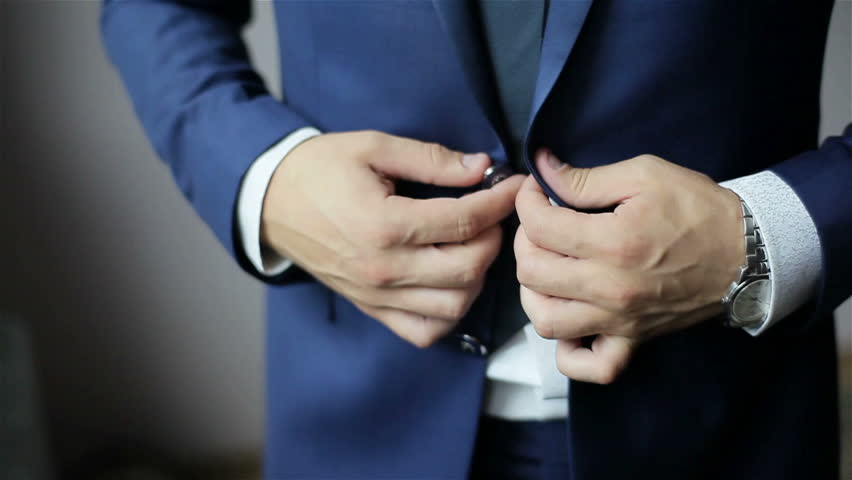 Buttoning a jacket. Stylish man in a suit fastening buttons on his jacket preparing to go out. Close up