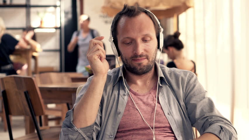 Young happy man in earphones listen to the music in cafe