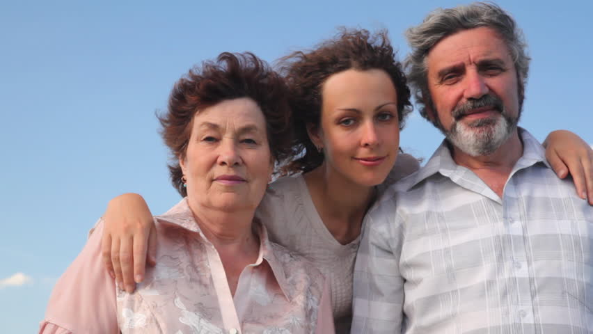 mature couple stands embracing with their adult daughter against sky in summer