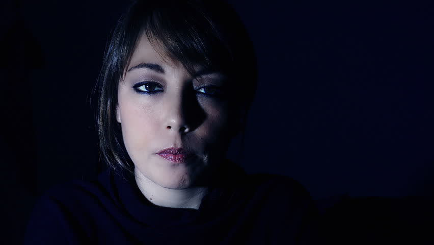 Thoughtful woman with dark background and side lighting   | Shutterstock HD Video #11044142