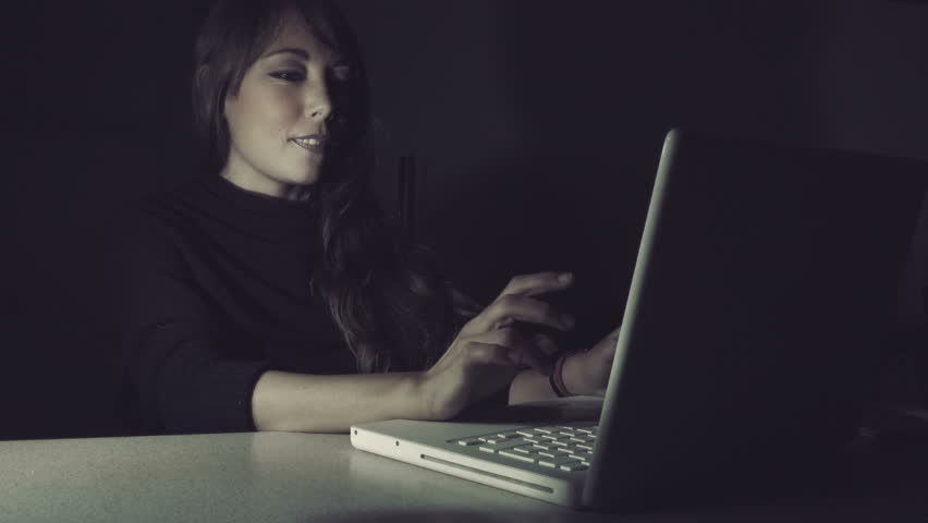 Smiling woman using the computer during the night: flirt, chat, social network 