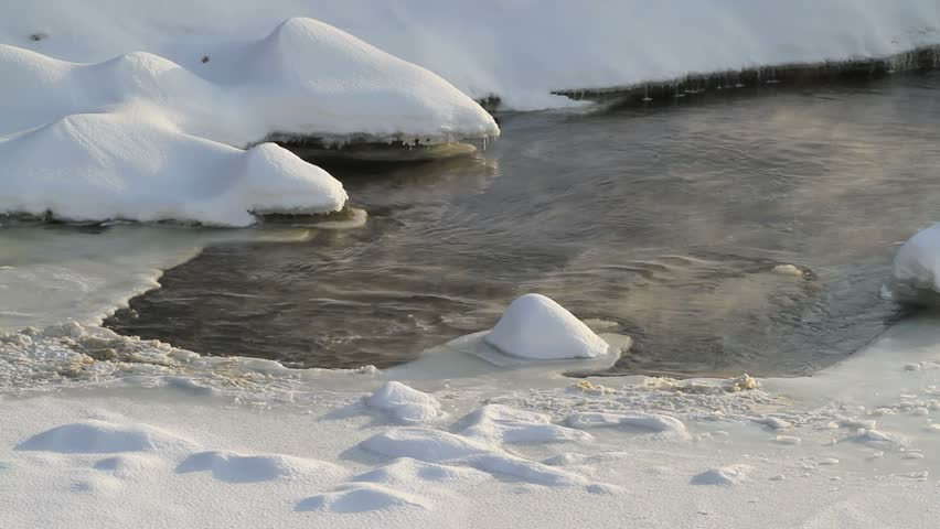 Wilderness river. Snow covered banks. Steam rises from open water as the river flows under the ice.