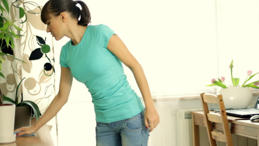 Woman having back pain while housekeeping