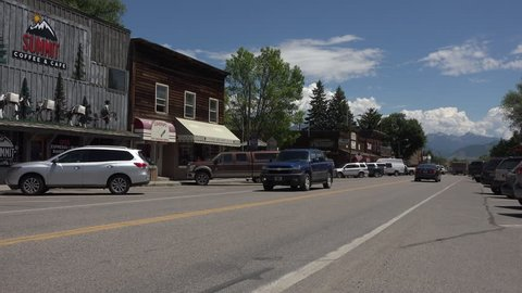 ENNIS, MONTANA - JUN 2015: Rural Ennis Montana main street business traffic 4K. Ennis is the center of a long historical ranching economy in the Madison River valley near Yellowstone National Park.