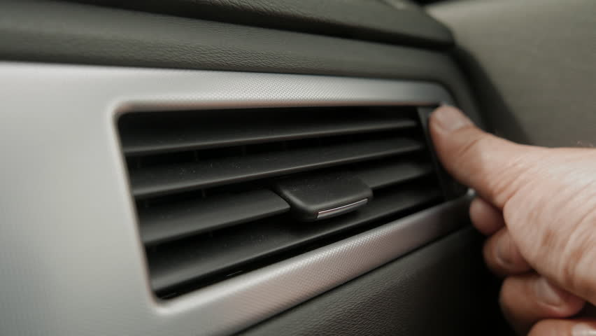 Hand turns up air-condition, AC, in car.