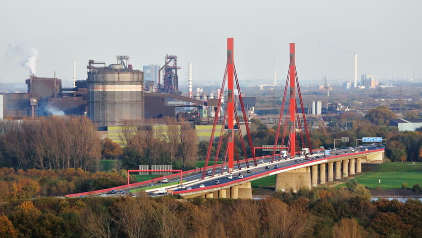 View to the A42 motorway bridge of Rhine River in Duisburg, Germany with a gasometer and steel industry in the background.