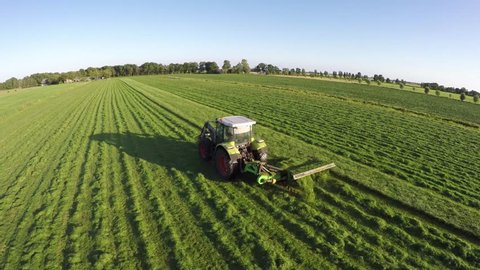Drone flight aerial bird eye view of tractor mowing grass from side of farmer on a beautiful green field and blue sky in the background helicopter view and using very high resolution 4k camera