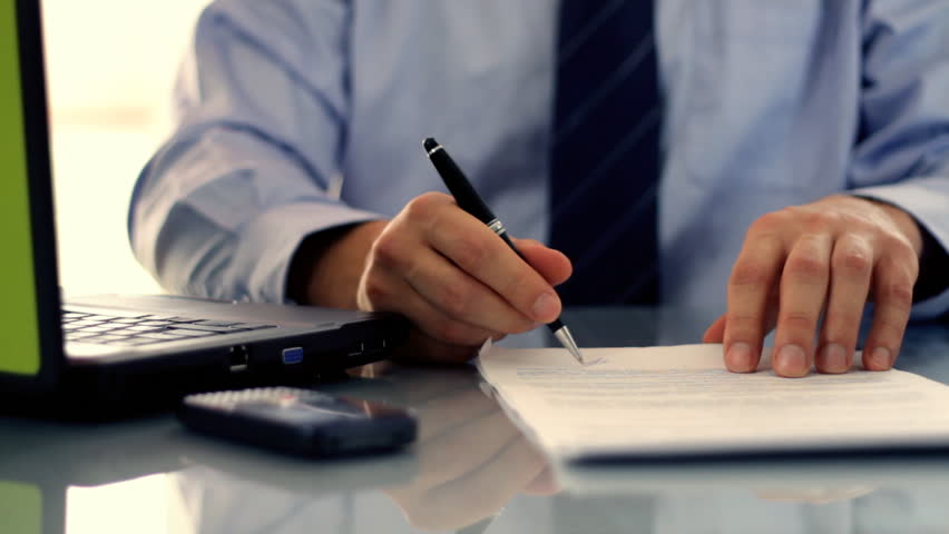 Businessman signing documents on reflective table