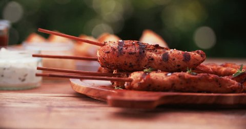 Classic summer meal with barbecued chicken skewers, and crisp white wine laid out on a vintage wooden table in a back yard