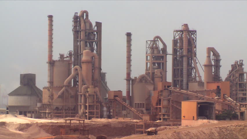 A pan of a working cement factory in an industrial area in Salalah in Oman, showing moving trucks and a port in the distance.