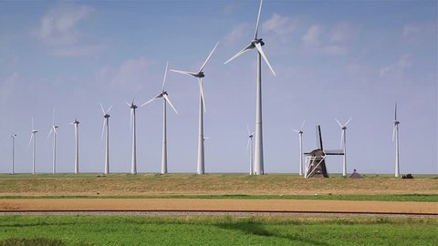 Modern wind turbines generating clean and renewable energy and the traditional, Dutch windmill Goliath.
