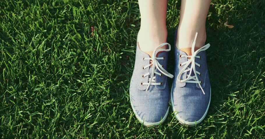 Female feet in sneakers gumshoes moving and posing on a sunlit green grass, close up. Woman's feet in blue jeans color sports shoes. Slow motion, 120fps. 4K, DCi.