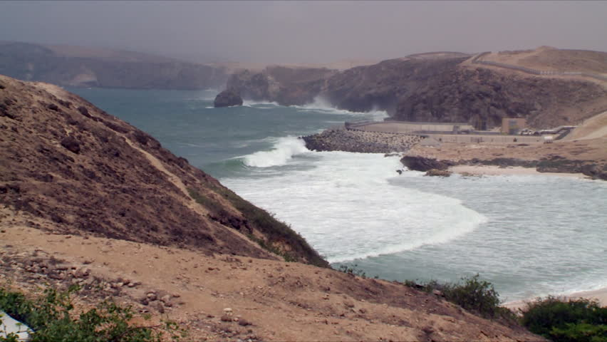 A pan showing the rocky, mountainous coast line of Salalah, Oman as the sea comes into a sandy white beach and waves crash into rocks in the distance